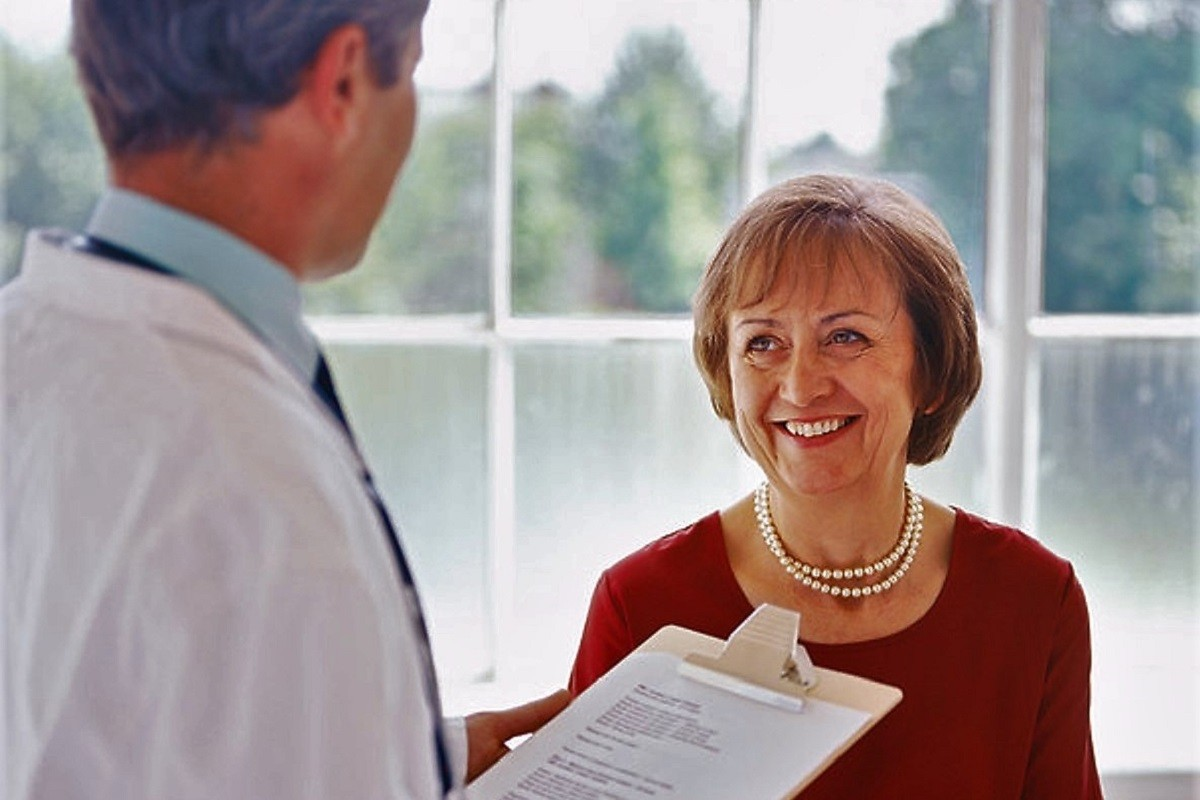 portrait of an elderly woman talking to a male doctor
