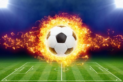 Abstract sports background - burning soccer ball above green football stadium at night