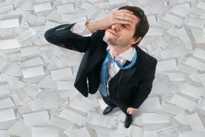 Businessman has headache. Disappointment and failure concept. A lot of documents and invoices around.