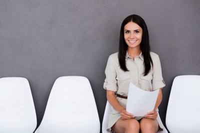 Successful job candidate. Confident young businesswoman holding paper while sitting on chair against grey background