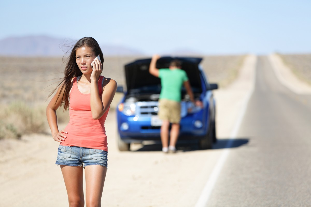 Car breakdown - woman phone calling auto service help. Neutral or negative expression on woman on mobile smart phone, while man trying to fix the car. Young couple on road highway in California, USA.