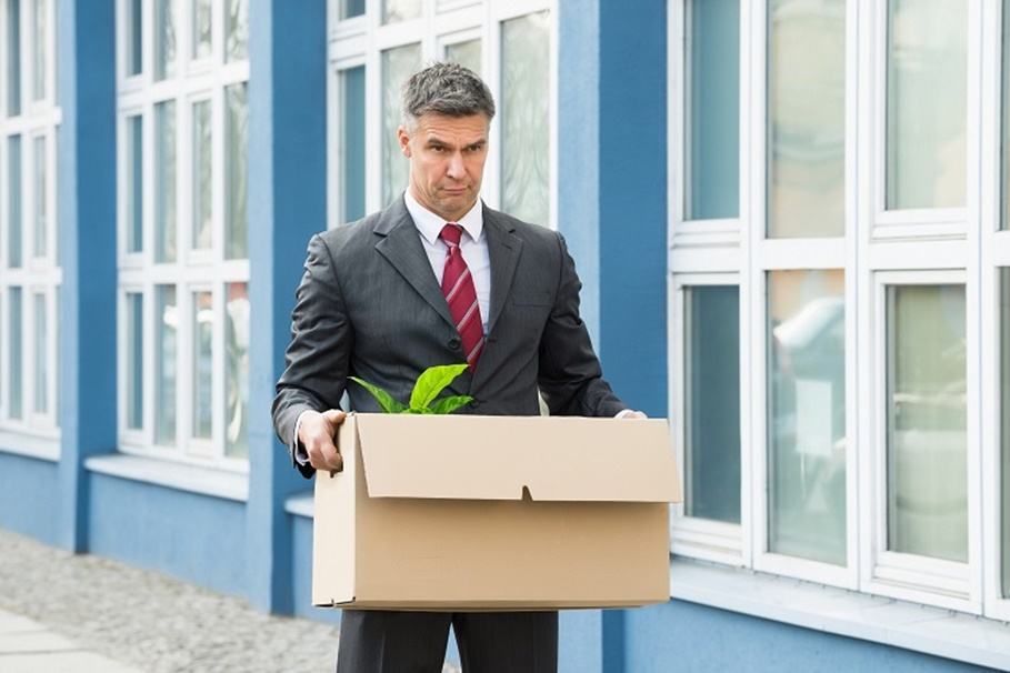 Sad Mature Businessman Carrying His Belongings In Box After Being Fired