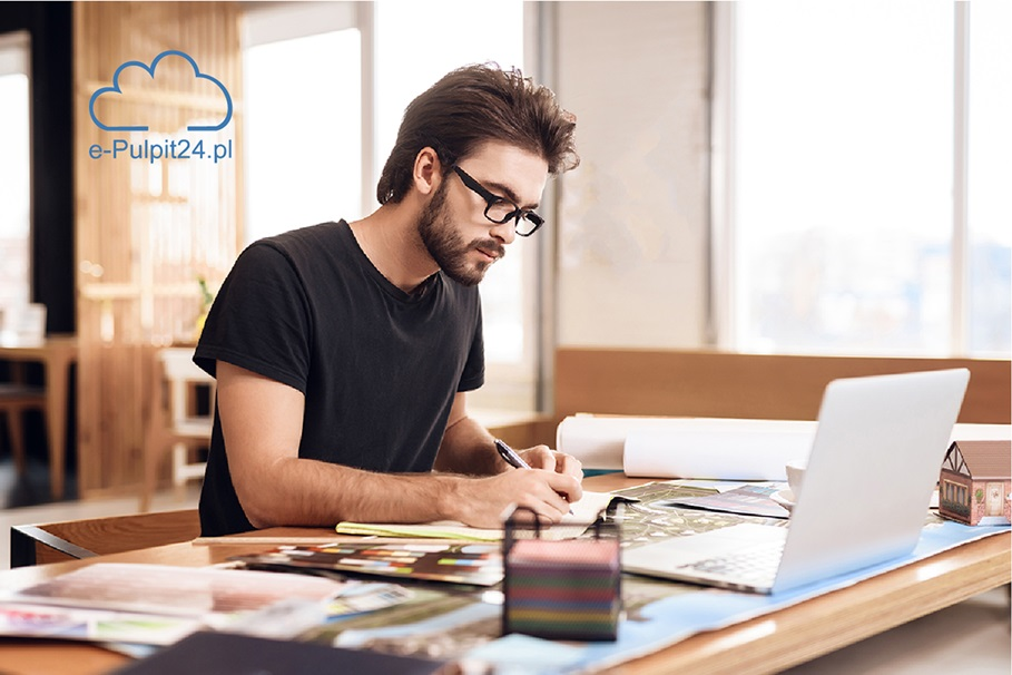 Freelancer bearded man in t-shirt taking notes at laptop sitting at desk.
