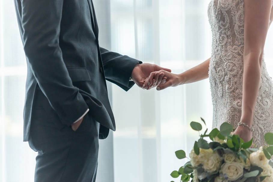 A shallow focus shot of a bride and groom holding hands with each other